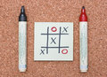 Tic tac toe game with red and black markers on cork Royalty Free Stock Images