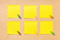 Tidy yellow post it collection set of six well ordered square blank notes with colored clips arranged on a wooden board and ready Royalty Free Stock Photo
