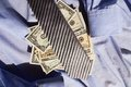 Tie and dollars lying on dolarach lying on a blue striped shirt Stock Photos