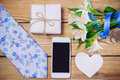 Tie, gift box, flowers with ribbon, cell phone on wooden table Royalty Free Stock Photo