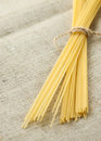 Tied spaghetti with rope on organic bagging. Selective focus Royalty Free Stock Photo