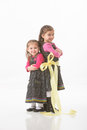Tied up sisters full length portrait of with a large yellow ribbon Stock Image