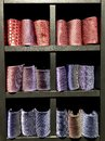 Ties, from red to purple, are folded into rolls on display shelves. Royalty Free Stock Photo