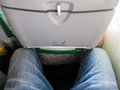 Tight legroom view on legs behind seat in commercial aircraft indicating in economy Royalty Free Stock Image