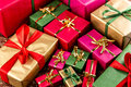 Tight shot brimming over with gifts plenty of wrapped presents in plain red green gold and magenta filling the frame shallow depth Royalty Free Stock Photography