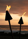 Tiki torches in the sunset Royalty Free Stock Photos