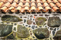 Tiled roof and wall decorated with stones detail of house red clay big small like mosaic exterior facade design of Royalty Free Stock Image