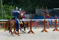 Tilting knights two armored ride at one another in a jousting match during a renaissance festival Royalty Free Stock Photos