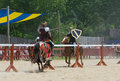 Tilting knights two armored ride at one another in a jousting match during a renaissance festival Royalty Free Stock Photography