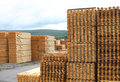 Timber or lumber yard with stacked pine planks in focus on foreground stacks Stock Images