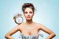 Time for action a beautiful vintage girl in a white wedding dress with a retro alarm clock on her shoulder in the morning Stock Photography