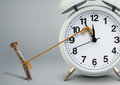 Time on alarm clock stop by nail, delay concept Royalty Free Stock Photo