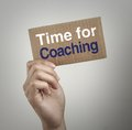 Time for coaching hand with brown card is showing with gray background Royalty Free Stock Image