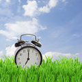 Time concept alarm clock in grass on blue sky Royalty Free Stock Photo