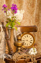 Time concept still life bouquet of hydrangea and phloxes on the old chair with clock and oil lamp Royalty Free Stock Photography