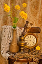 Time concept still life with yellow flowers antique clock and oil lamp Stock Photography
