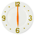Time of dinner, сlock from plate, carrots and green peas Royalty Free Stock Photo