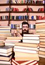 Time flow concept. Man on surprised face holds hourglass while studying, bookshelves on background. Man, scientist in Royalty Free Stock Photo