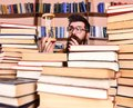 Time flow concept. Teacher or student with beard studying in library. Man, scientist in glasses looks at hourglass. Man Royalty Free Stock Photo