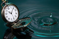 Time flow concept vintage pocket watch on water with falling drop Stock Photos
