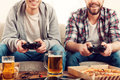 Time for games cropped image of two young men playing video while sitting on sofa Royalty Free Stock Images