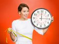 On time great fitness result portrait young attractive happy fit woman holding clock measuring her waist with tape isolated red Royalty Free Stock Photos