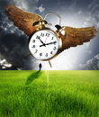 Time and man a walking into the horizon as a clock with wings flies over in a dark cloudy sky Stock Images