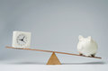 Time is money clock and piggy bank balancing on a seesaw Royalty Free Stock Image