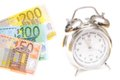 Time is money euro banknotes infront of an out of focus alarm clock as a visualisation of the saying Royalty Free Stock Images