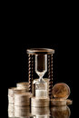 Time and money euro coins hourglass on black background studio shot Stock Image