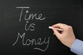Time is money hand writing on a blackboard a concept for improving efficiency and management in your business and personal Stock Images