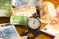 Time is money pocket watch with various banknotes in the background Royalty Free Stock Images