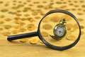 Time is money still life with small pocket watch golden looking coins and magnifying glass Stock Photos
