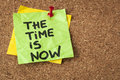 The time is now motivational reminder on a green sticky note Stock Photography