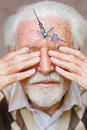 Time passing clock hands placed on elderly mans forehead Stock Image