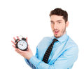 Time s ticking closeup portrait business man worker guy holding clock looking anxiously pressured by lack running out of isolated Royalty Free Stock Image