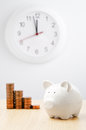 Time for savings descending money stacks next to a piggy bank Royalty Free Stock Photos
