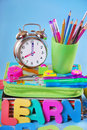 Time for school concept equipment with alarm clock books notes pencils and apple on blue background Royalty Free Stock Images