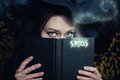 It is time for sorcery pretty witch with spells book in the forest Stock Images