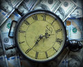 Time spent a clock and money one hundred dollar bills Stock Image