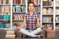 Time to chill beautiful young woman keeping her eyes closed and meditating while sitting at the library Royalty Free Stock Photos