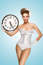 Time to party a cute pin up girl with a vintage hairstyle holding an office wall clock and showing the Royalty Free Stock Images