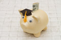 Time to start saving for college, A piggy bank and graduation ca Royalty Free Stock Photo