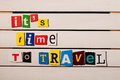 Time to Travel - written with color magazine letter clippings on wooden board Royalty Free Stock Photo