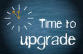 Time to upgrade concept drawing on a clock next the words on a blackboard or chalkboard business Stock Photos