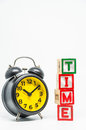 TIME word wooden block arrange in vertical style with black retro alarm clock on white background and selective focus Royalty Free Stock Photo