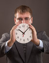 Time young man in a suit holding a clock Stock Photo