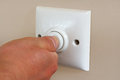 Timed light switch pressing an energy efficient designed to save electricity and reduce power usage Stock Image