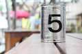 Tin can with number on wooden table Stock Images