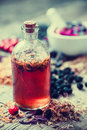 Tincture bottle and mortar of healing herbs on background. Royalty Free Stock Photo